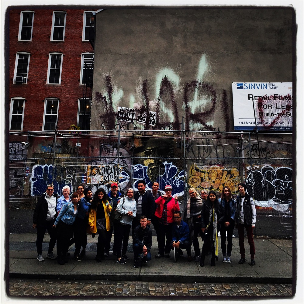 The whole gang posing in front of an empty SoHo lot-- Jude is the first person in the left of the photo.