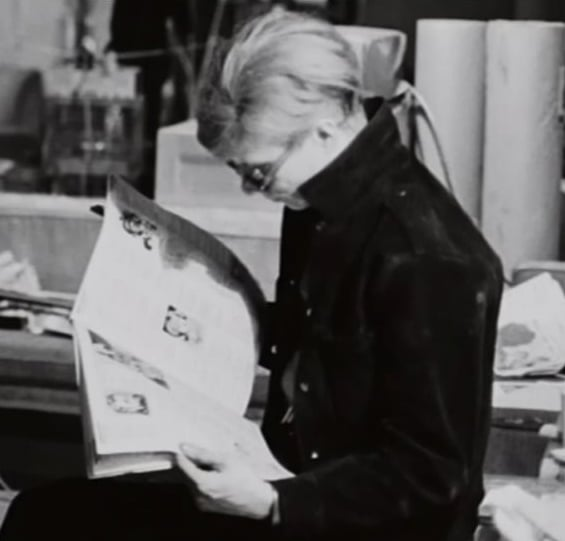 Andy Warhol reading, or at least pretending that he is.