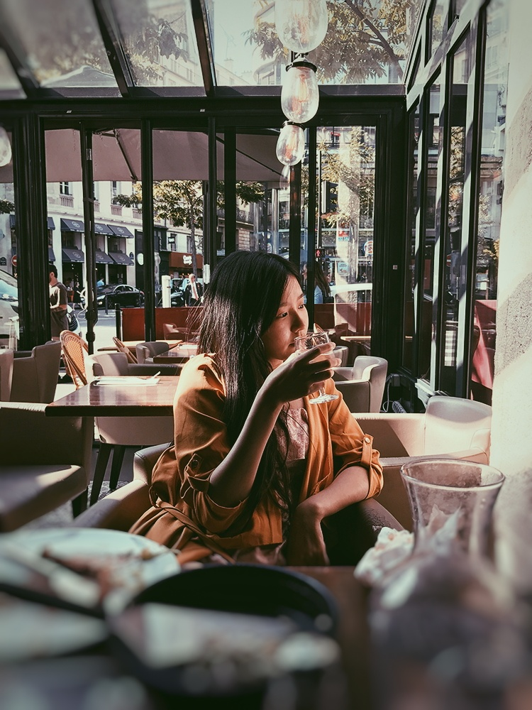 Tiffany taking the time to enjoy the moment in a Parisian café.