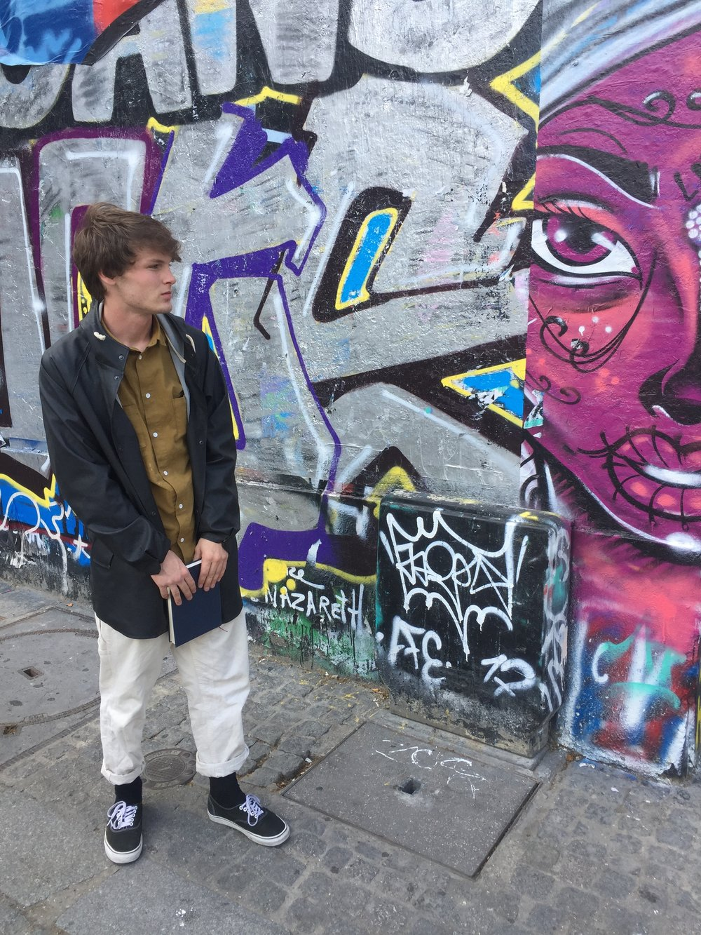 Lukas immersed in the street art and urban vibe of Paris.