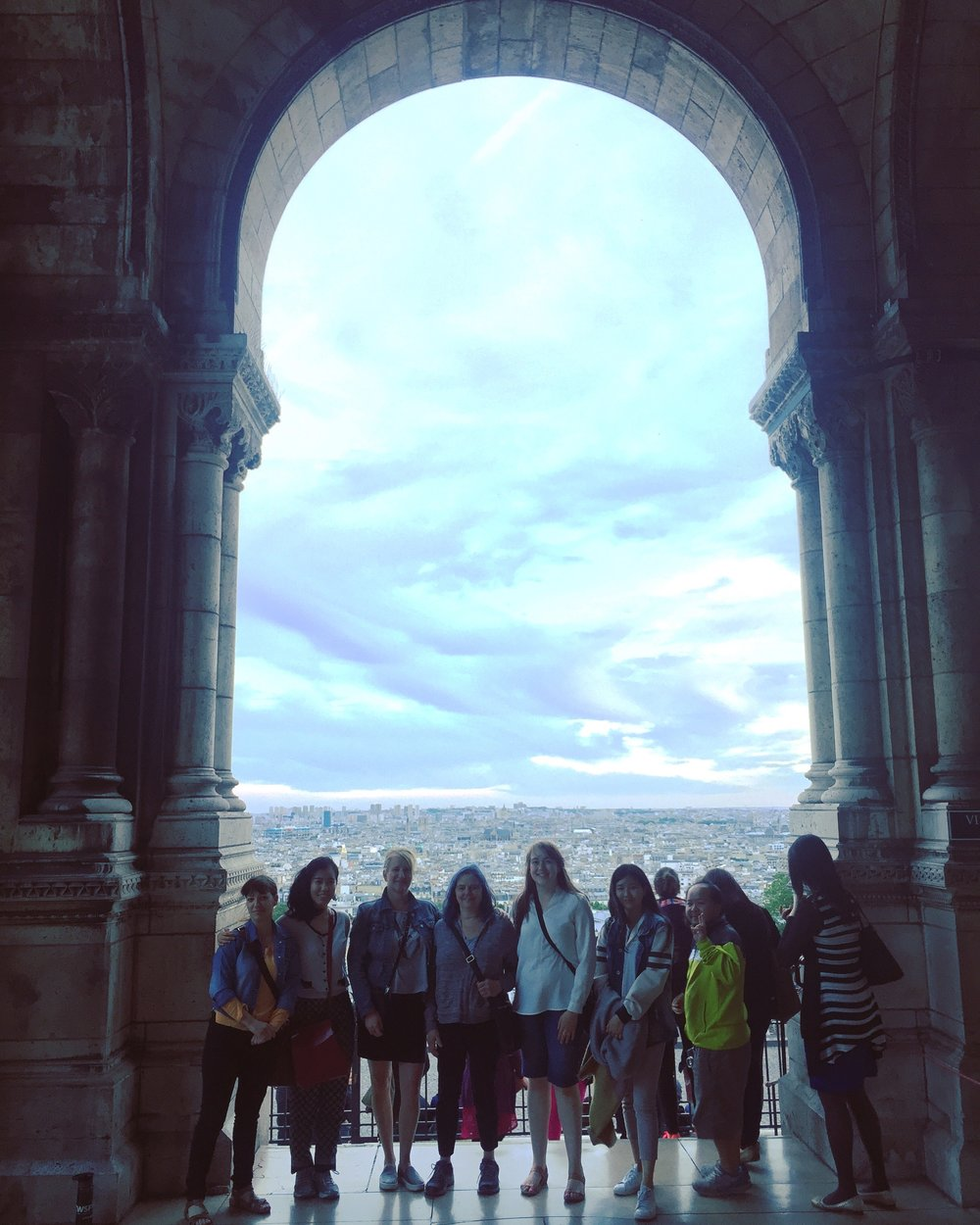 Group picture overlooking the city at sunset from the Sacre Coeur Basilica portico in Montmartre-- Josie at center.