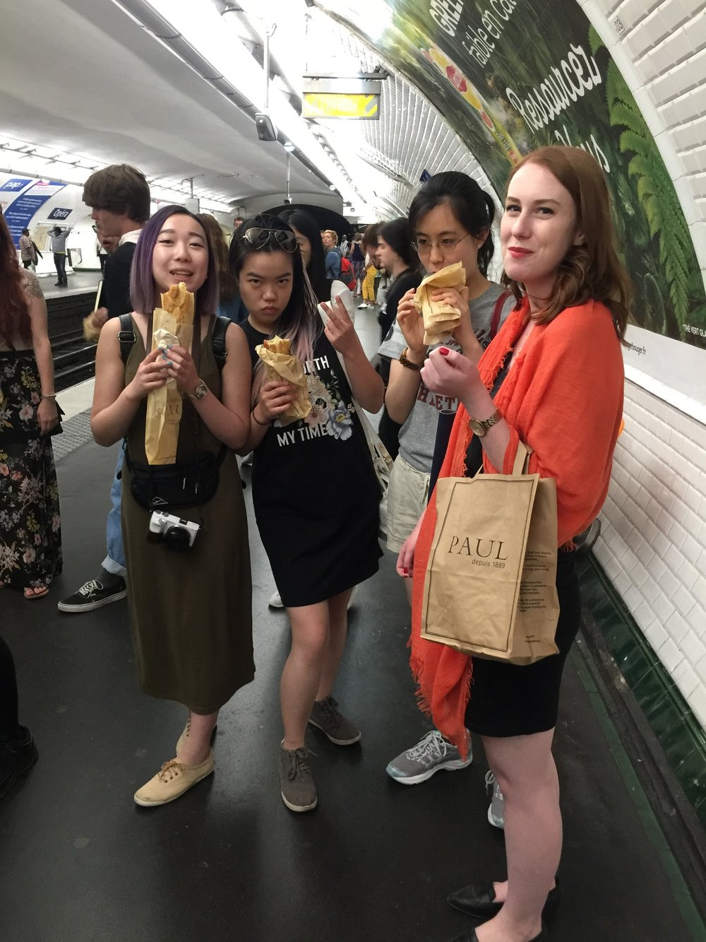 Jenny, Zoe, Alice, and Ashley enjoying on-the-go sandwiches while waiting on the Metro.