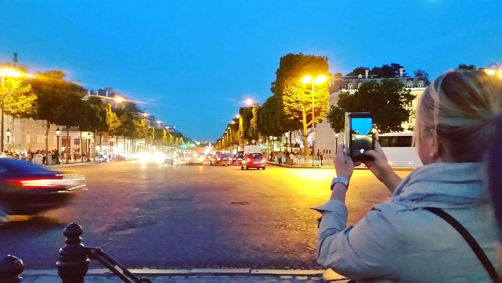 Dorothy photographing the Champs-Élysées after touring the Arc de Triomphe.