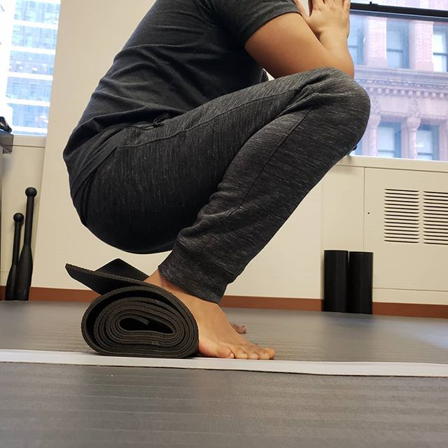 Have a deep squat that needs some improvement? Me too. Put a rolled up yoga mat under your heels for some help. This allows you to shift your weight backwards to improve your hinge and also helps those of us with less ankle dorsi flexion. Good mobility exercise to do while watching TV. Make sure to breathe! #deepsquat #physicaltherapy #mobility #resetpt #movement #humanmovement