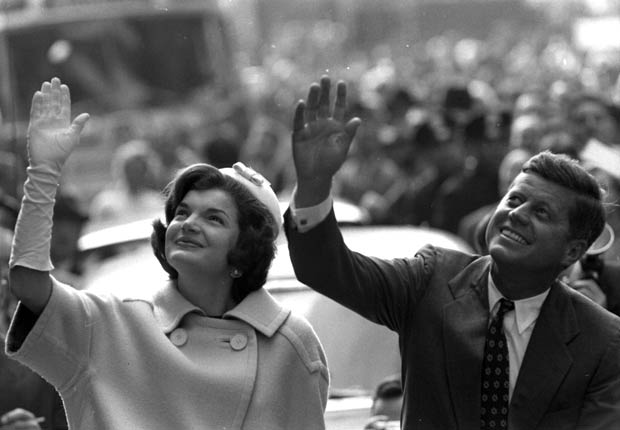 Jackie Kennedy and JFK waving to a crowd from the streets of New