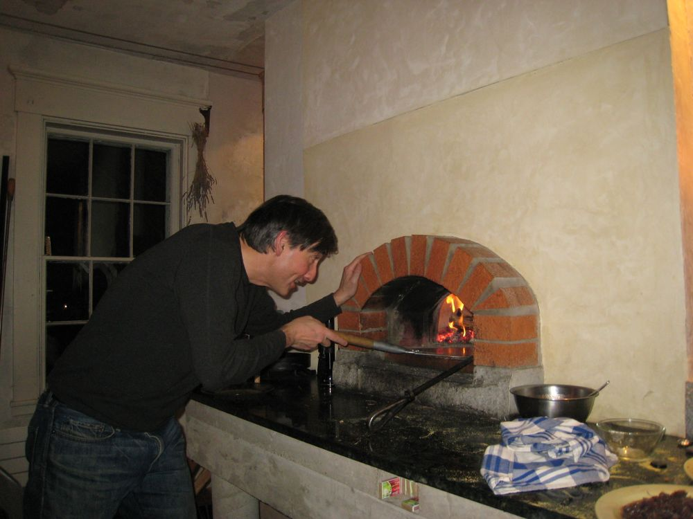 stoking the fire in the pizza oven