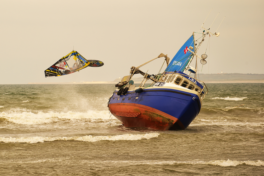 The first day of the KIA Cold Hawaii PWA World Cup in Klitmøller. Ricardo Campello from Venezuela forward loop. The night before a small fishing boat has run aground right off the beach.