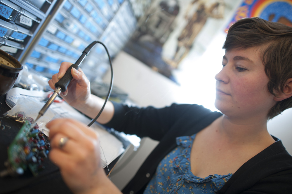 Emma the circuitry nerd and electronics-wizard works her magic in a coat closet, meticulously and lovingly soldering the pedal brains to spark the soaring sounds of rock & roll.