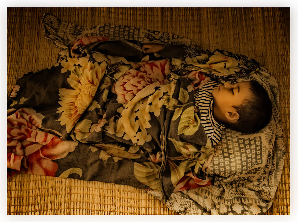Child sleeping on hospital floor, Bangladesh.
