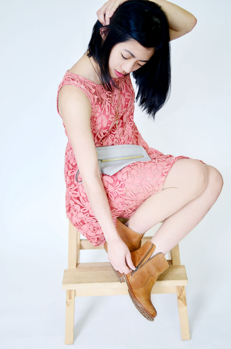 Elysia wears a thrifted Free People lace dress in salmon pink, styled with Olukai boots and an Urban Outfitters clutch.