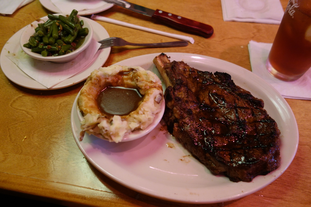 20 oz. bone-in ribeye with green beans, mashed potatoes with brown gravy, and unsweetened iced tea