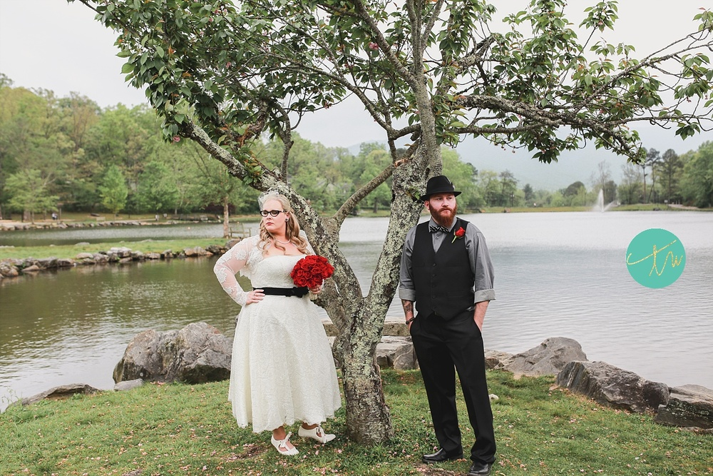 bride and groom poses at lake