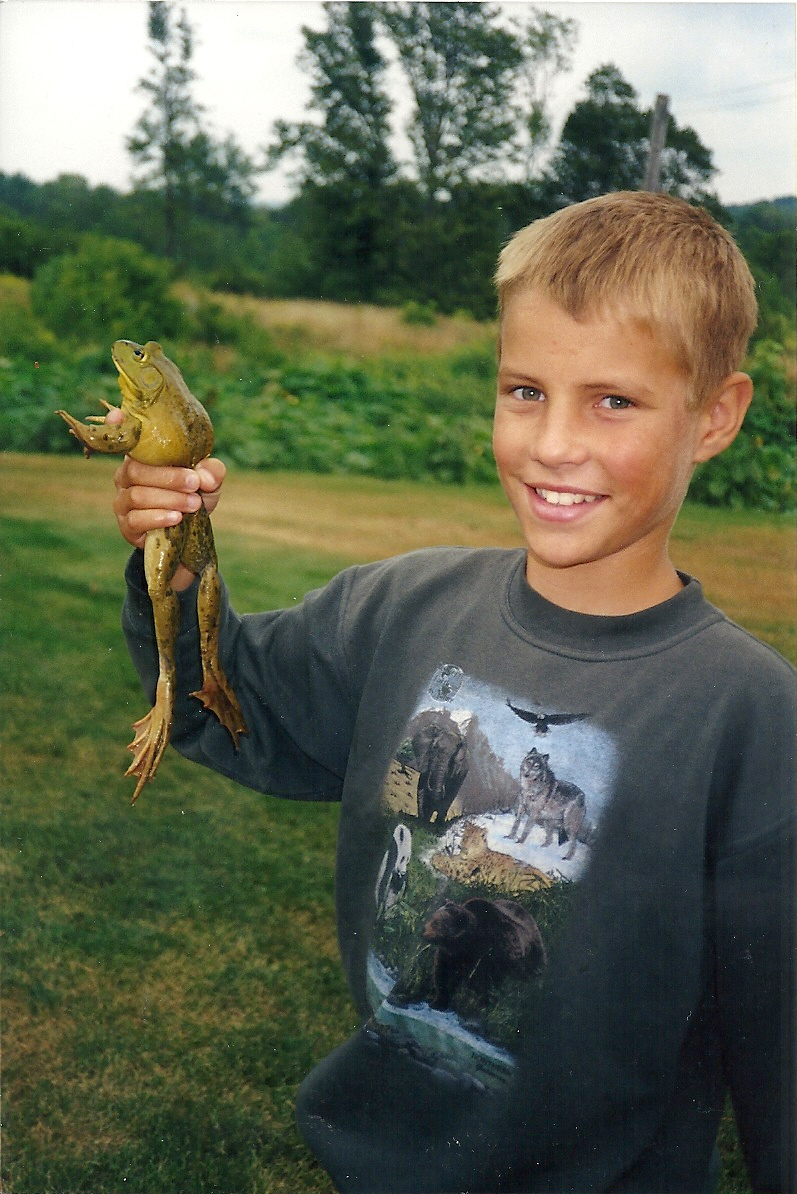 Younger me showing off my catch of the morning in the pond, asizeable bullfrog.