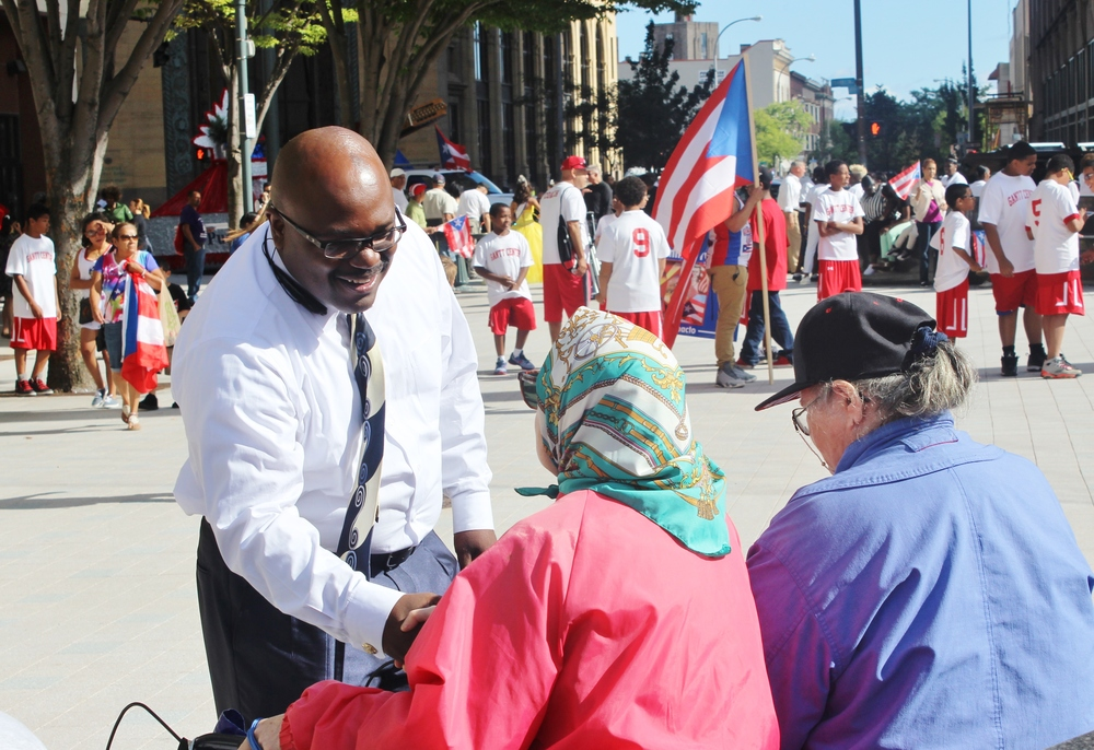 Legislator Flagler-Mitchell greets spectators before the 2015 Puerto Rican Parade.