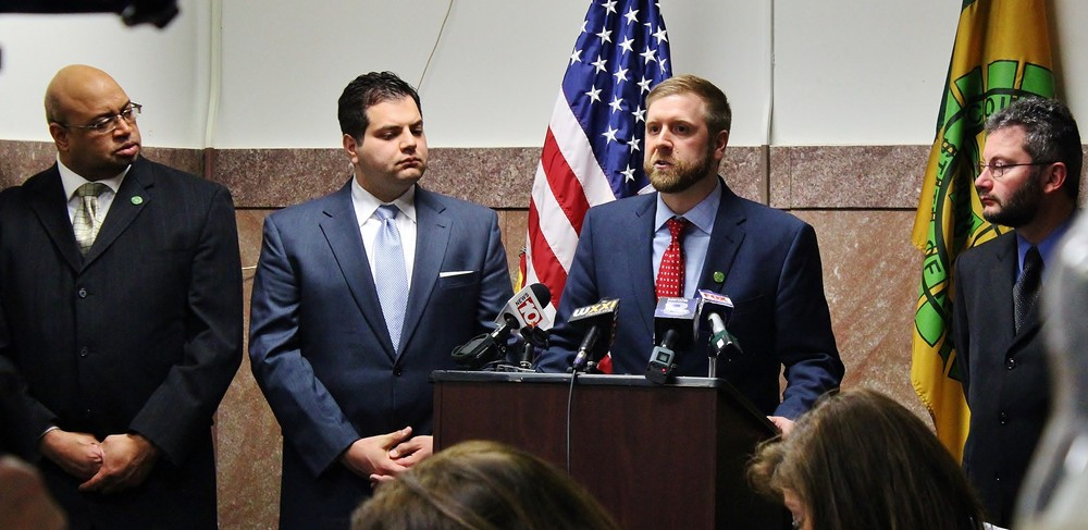 Legislator Mark S. Muoio (at podium) discusses his legislation, joined by (L to R) Assistant Minority Leader John Lightfoot and Legislators Joseph D. Morelle, Jr. and Joshua Bauroth.