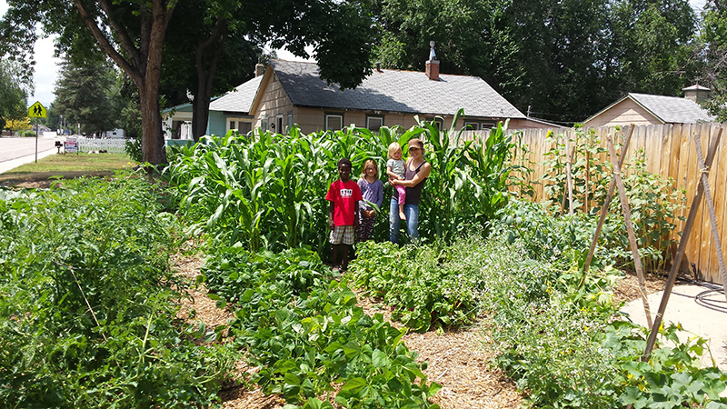 Lynn with her three kids, Kevin, Reese and Harper in front of the thriving corn!.