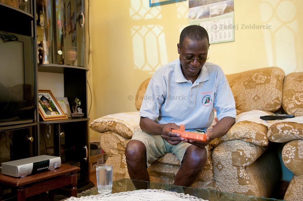 Dr. Stephen Watiti takes antiretroviral drugs at home.