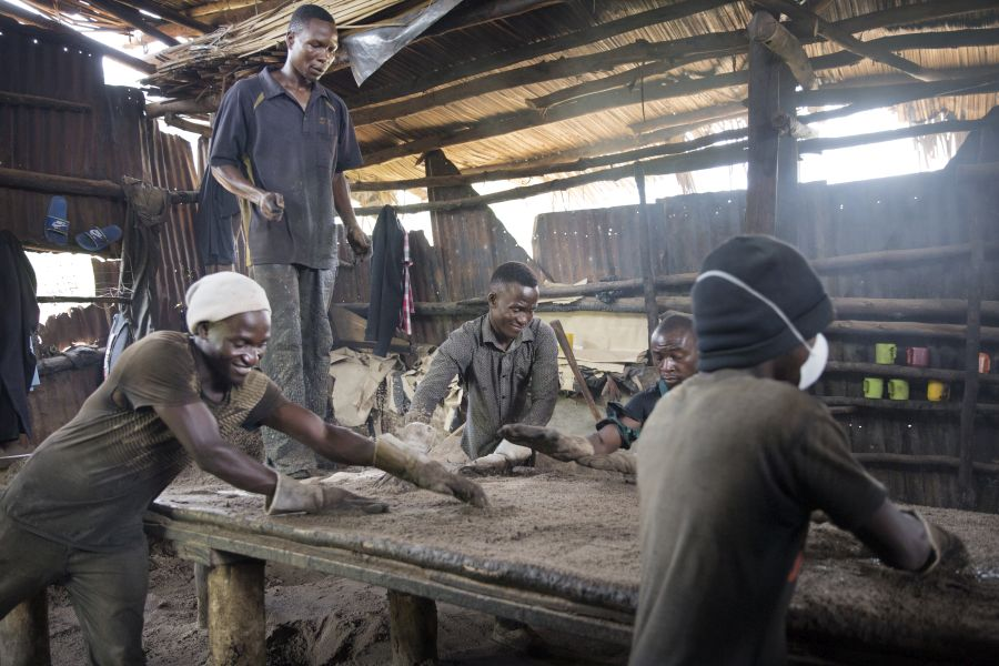 In his father's factory, Peter and other workers make tar paper used in construction.