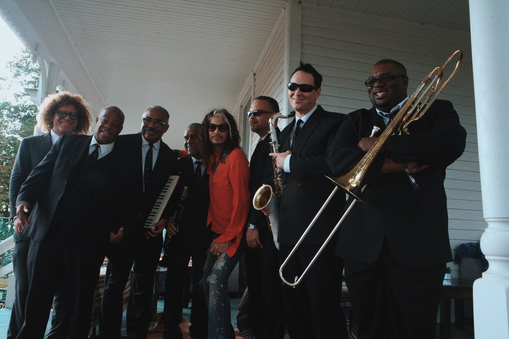 Steven Tyler poses with Preservation Hall Jazz Band in the media tent