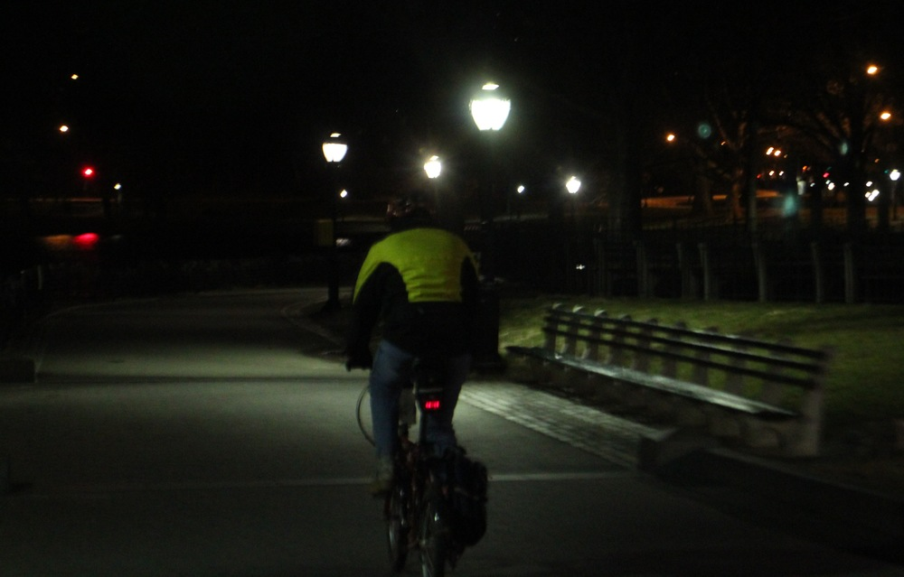 Cyclist at night (rear) on a lit city road