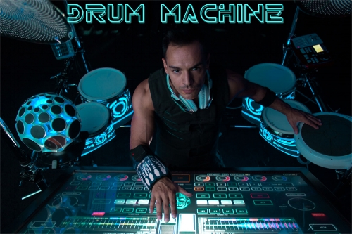 Drum Machine - With a degree in music and production, Shannon Ellinas continues to innovate and change the industries traditional view of drumming. Utilizing a one-of-a-kind 55'' transparent Holoscreen, surrounded by 13 LED Light drums and cymbals, the South African Percussive Performance DJ combines the latests in music, technology, and unique Drum Machine showmanship.