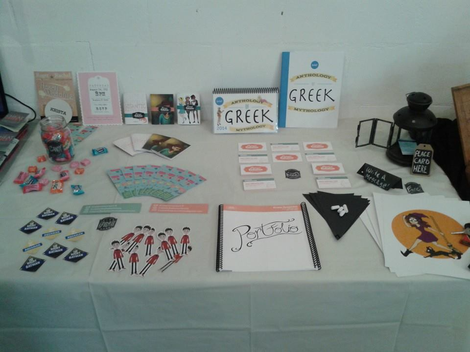 My display table with various Self Promotional items including: Business Cards, Prints, Stickers, Sketchbooks and Contact Bookmarks