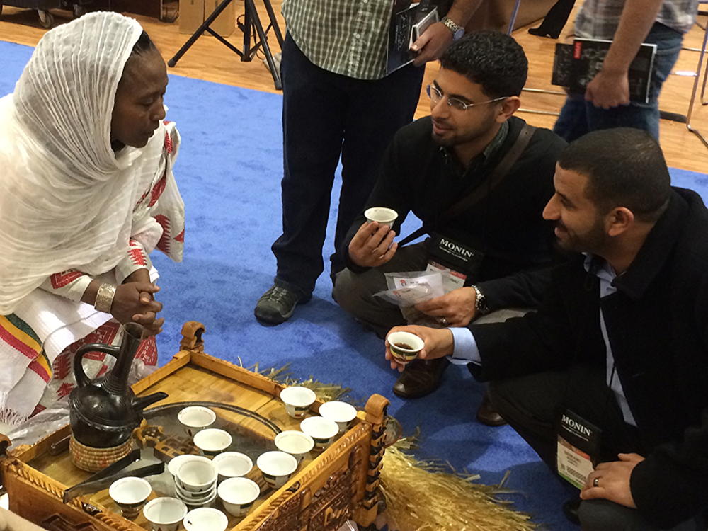 Mokhtar (left) and Ibrahim (right) meet with an Ethiopian Farmer at the 2014 Speciality Coffee Association Conference