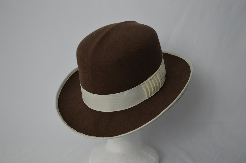 The Chimera Fedora In classic Greek mythology the Chimera was a beast made up of the parts of many different animals. As this hat combines styles of many hats, the name Chimera seemed fitting. The crown is an optimo crown, typically only seen in summer panama hats. The brim is blocked using a western block, giving a wide dramatic flair. And the hat band detail is inspired by a bow on a vintage fedora from the 40s. All these elements come together to form a new silhouette of hat; a beast of many parts.