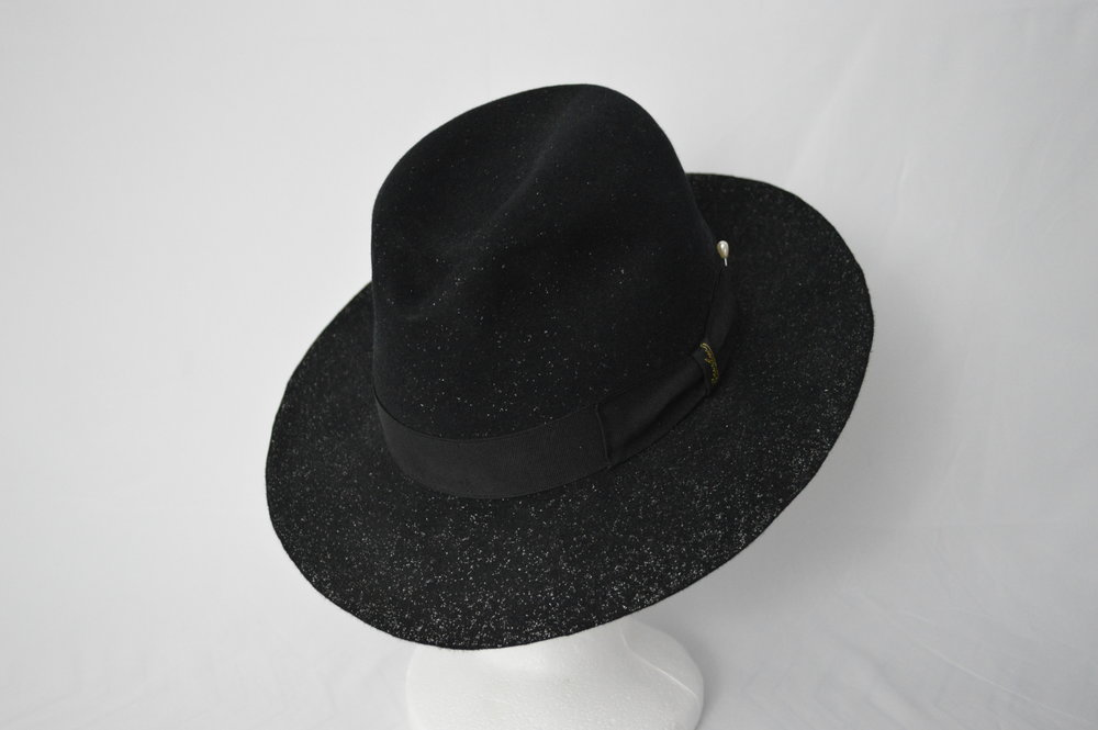 The Stardust Fedora Silver glitter felted into the dark black of this hat gives the impression of stars in the night sky. The Stardust Fedora is a high quality fur felt blocked into a classic centerdent shape. The hat is trimmed with a black grosgrain hat band and stuck with a pearl hat pin to match the shine of the glitter in the felting.