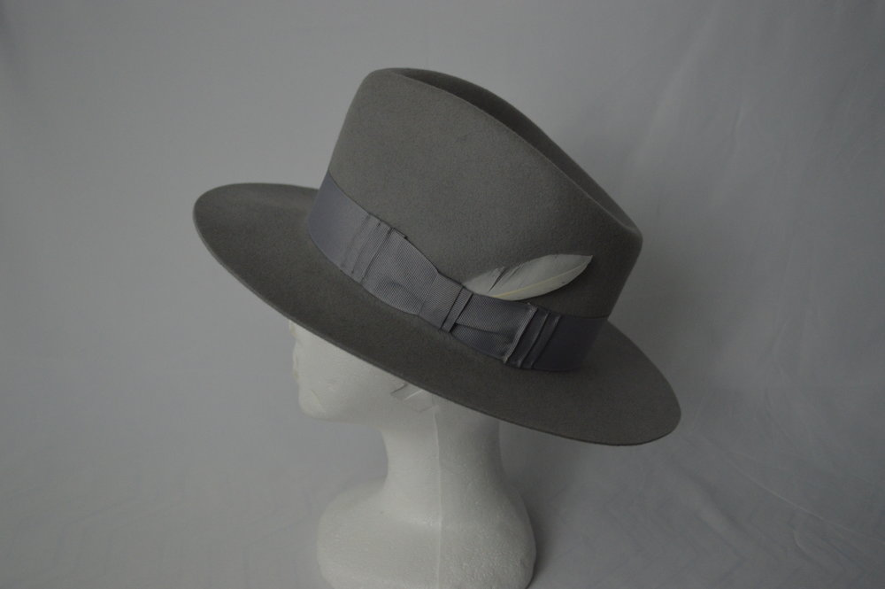 "The Hercules Fedora When looking for classic style icons, Howard Hughes is a name that often comes to mind. A genius inventor and avid hat-wearer, Hughes was an inspiration to many. This hat takes it's name from possibly his most famous plane the Hughes H-4 Hercules, or as it's more commonly known, the ""Spruce Goose"". This beautiful grey fedora has a classic teardrop crown which slopes dramatically towards the back of the hat. The grosgrain band has a folded bow detail and a feather tucked behind as a symbol of the many flights Hughes was responsible for."