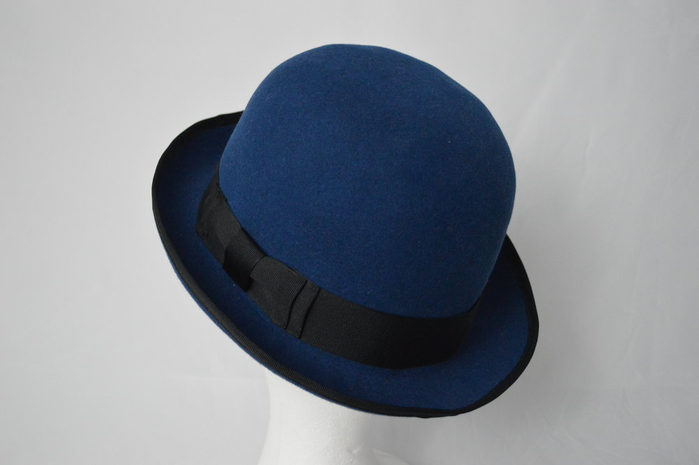 The Chaplin Bowler Taking inspiration from one of the icons of the silver screen, Charlie Chaplin, this little bowler is made from a high quality fur felt. Unlike Chaplin's classic black bowler, this one comes in a rich blue colour, trimmed with a black hat band and edge binding. The combination of these colours gives the hat a much more modern look while still retaining that classic bowler style.