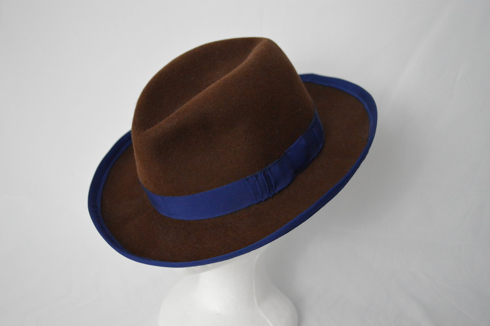 The Emmet Fedora A classic style centerdent fedora made from a soft fur felt. Trimmed with a wide grosgrain edge binding and matching hat band with a modern geometric bow. The blue trim perfectly complements the rich brown colour of the felt.