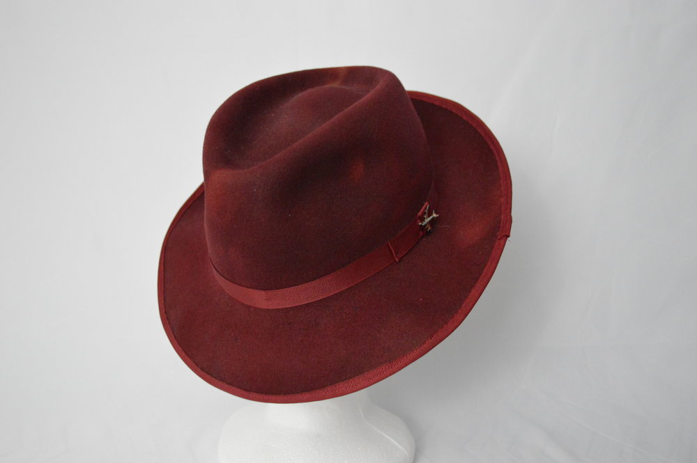 The Wilbur Fedora Named after Wilbur Wright, the elder of the two Wright brothers. The felt on this hat was hand-dyed giving it a unique textured look of deep burgundies and reds. It is hard blocked into a classic teardrop shape and trimmed with a thin grosgrain hat band. It also features a small airplane detail in honour of the brother's achievement in creating and piloting the first airplane.
