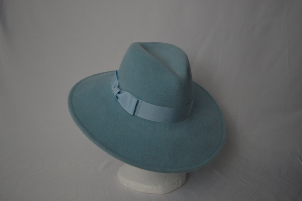 The Joanne Fedora Modeled after the large fedora worn by Lady Gaga on her Joanne album cover, this hat is made from a soft velour fur felt. The beautiful pastel blue gives it a light look which pairs beautifully with lots of styles. Trimmed with a wide grosgrain bow with a frayed edge for a unique finish.