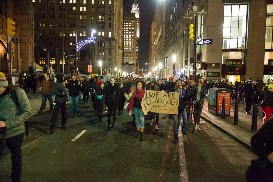 Protestors march south on Broadway past Wall St.