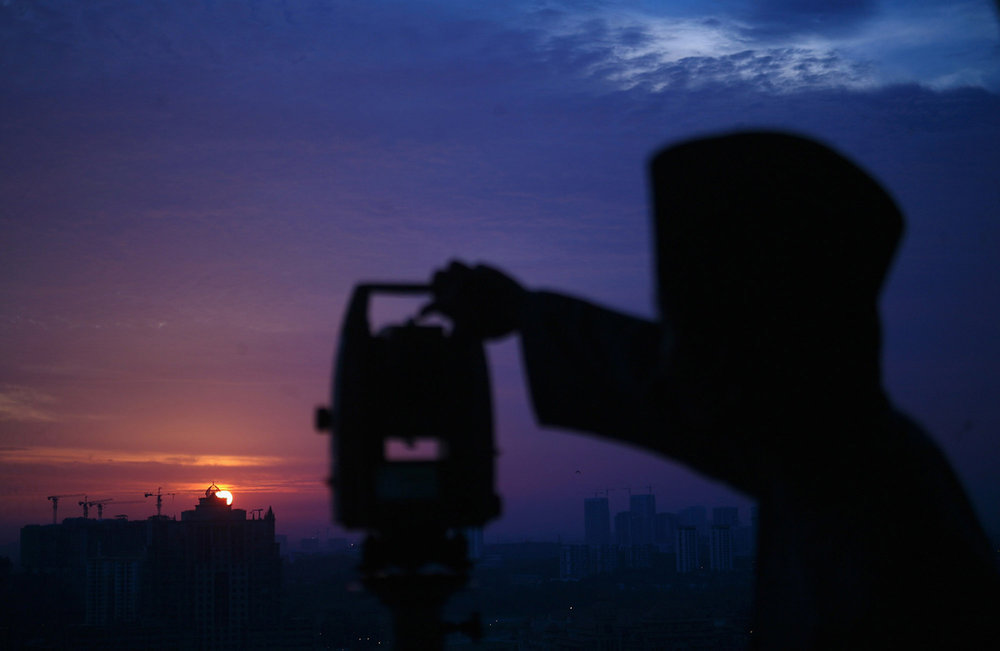 """An officer of Malaysia's Islamic authority uses a telescope to perform """"rukyah,"""" the sighting of the new moon of Ramadan, in Putrajaya, outside Kuala Lumpur, on June 5, 2016. Muslims scan the sky at dusk in the beginning of the lunar calendar's ninth month in search of the new moon to proclaim the start of Ramadan, Islam's holiest month during which observant believers fast from dawn to dusk. From The Atlantic, 'Images of Ramadan 2016. https://www.theatlantic.com/photo/2016/06/images-of-ramadan-2016/486212/"""