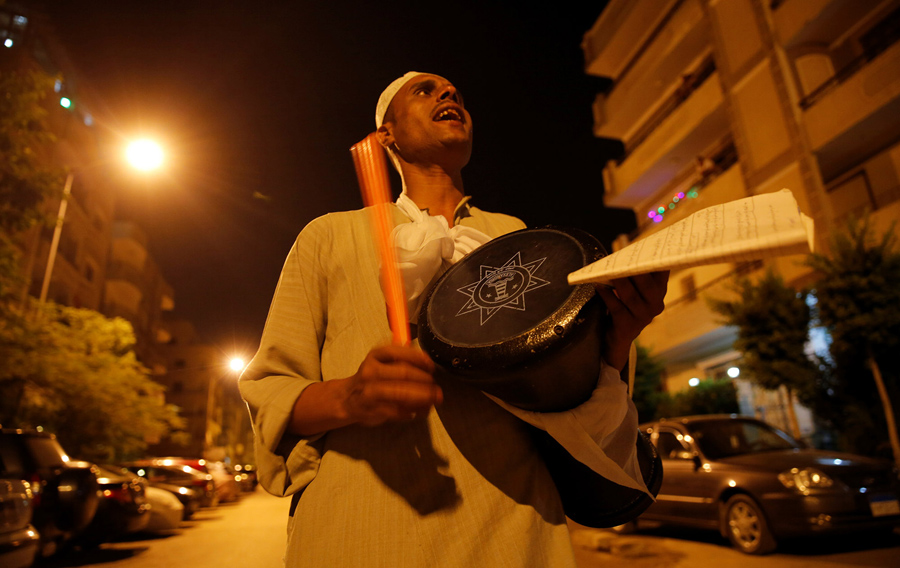 El Mesaharty Hussien, 40, wakes up residents for their pre-dawn meals during the first day of Ramadan in Cairo, Egypt, on June 6, 2016.madan in Cairo, Egypt, on June 6, 2016.  From The Atlantic, 'Images of Ramadan 2016. https://www.theatlantic.com/photo/2016/06/images-of-ramadan-2016/486212/