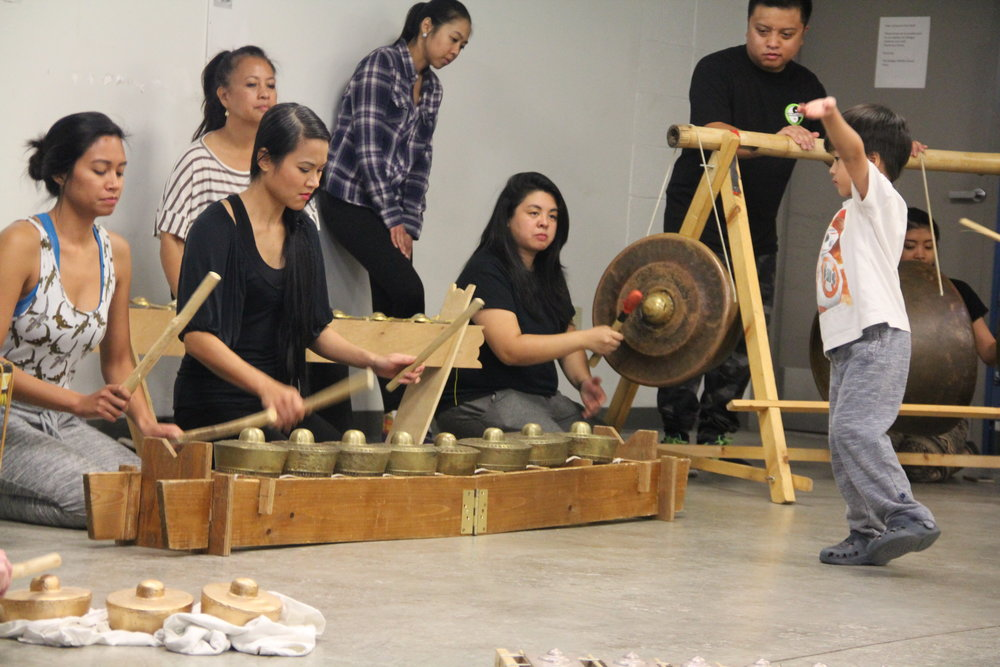 Participants have a hand at playing the  kulintang  and the gong, while a young participant practices  pangalay .