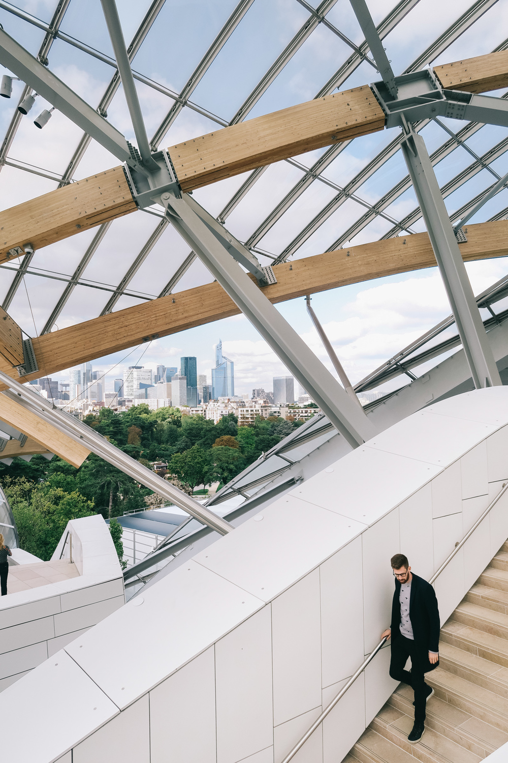 Fondation Louis Vuitton in Paris, wearing COS coat, Kenzo sweatshirt, Frame Denim, and Ecco shoes