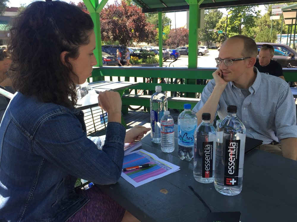 """Above and below: Our Purchasing Coordinator Eileen meets with Evan, an Environmental Analyst from the City of Boise to review our water bottle selection. Evan gives each bottle the """"crinkle test"""" to help determine whether or not it is recyclable under the new guidelines."""