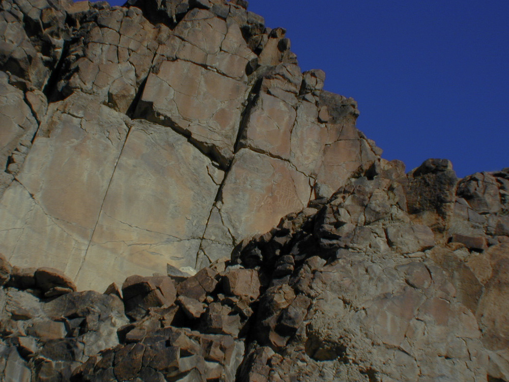 The first petroglyph. It is faint and high up the rock face.