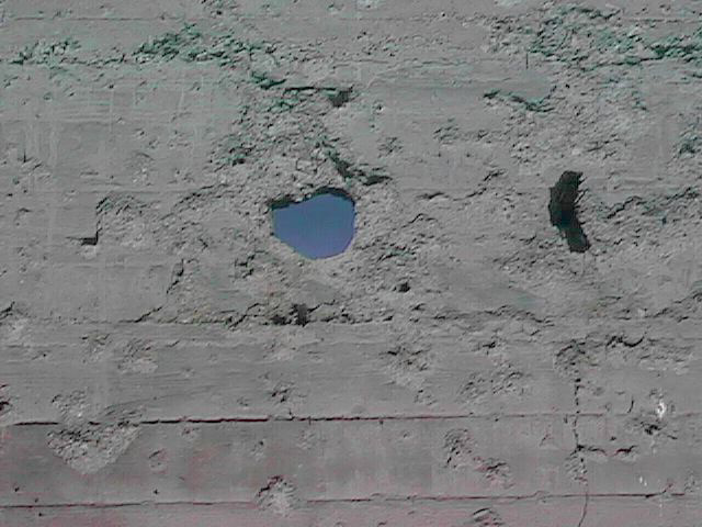 Mysterious hole blasted in concrete wall