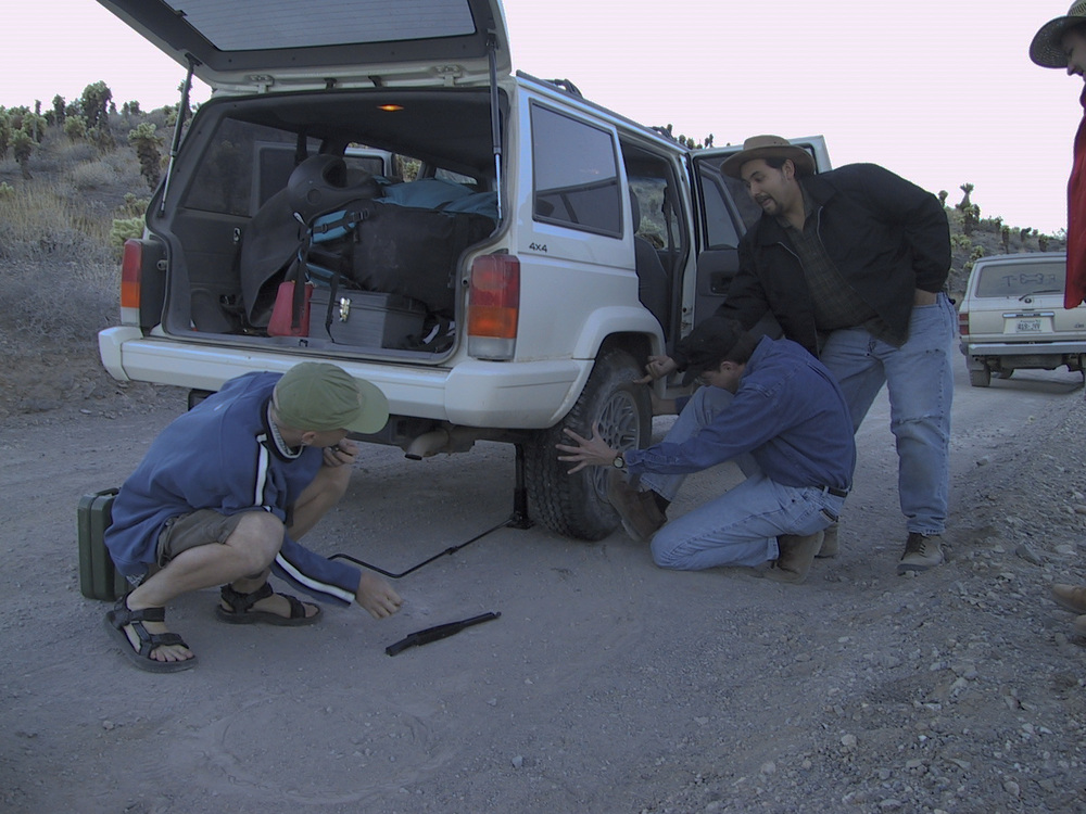 "Dwight decides to ""lift a finger"" and help with the tire changing."