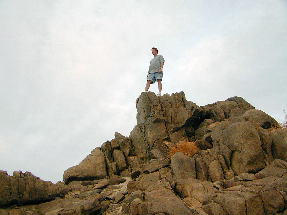 Matt climbs on rocks that overlook the dunes.