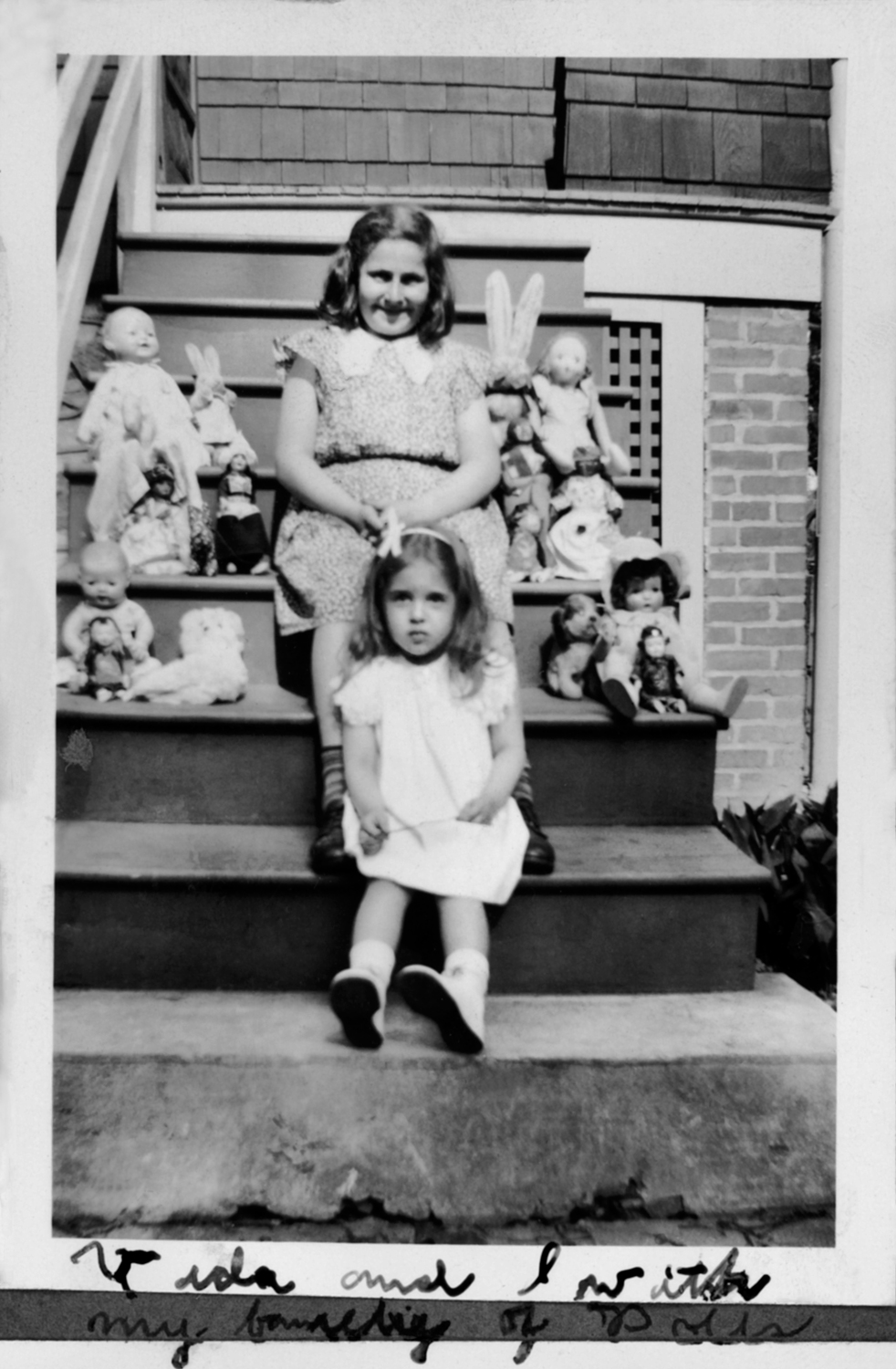 """Anne with her cousin Vida and her """"family of dolls"""" (from her photo album)"""