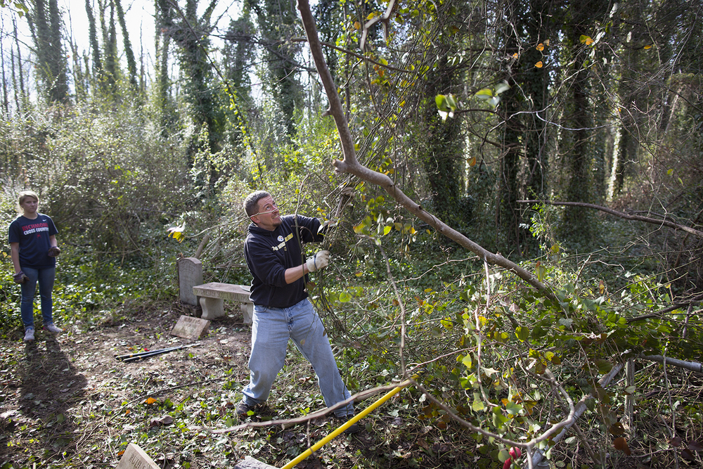 Volunteer Justin tugs at vines ensnaring tree branches during East End Cemetery work day, January 2015. ©brianpalmer.photos 2015
