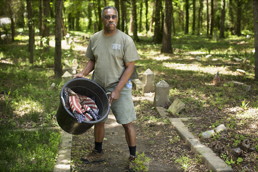 Scoutmaster Alan Meekins gathered soiled American flags and planted fresh ones on veterans' graves for Memorial Day. Photo: BP