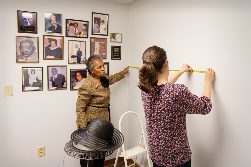 Ann Jones and Erin rehang photos on the walls of Mt. Pilgrim Baptist Church's newly constructed wing, Williamsburg, VA, April 10, 2016
