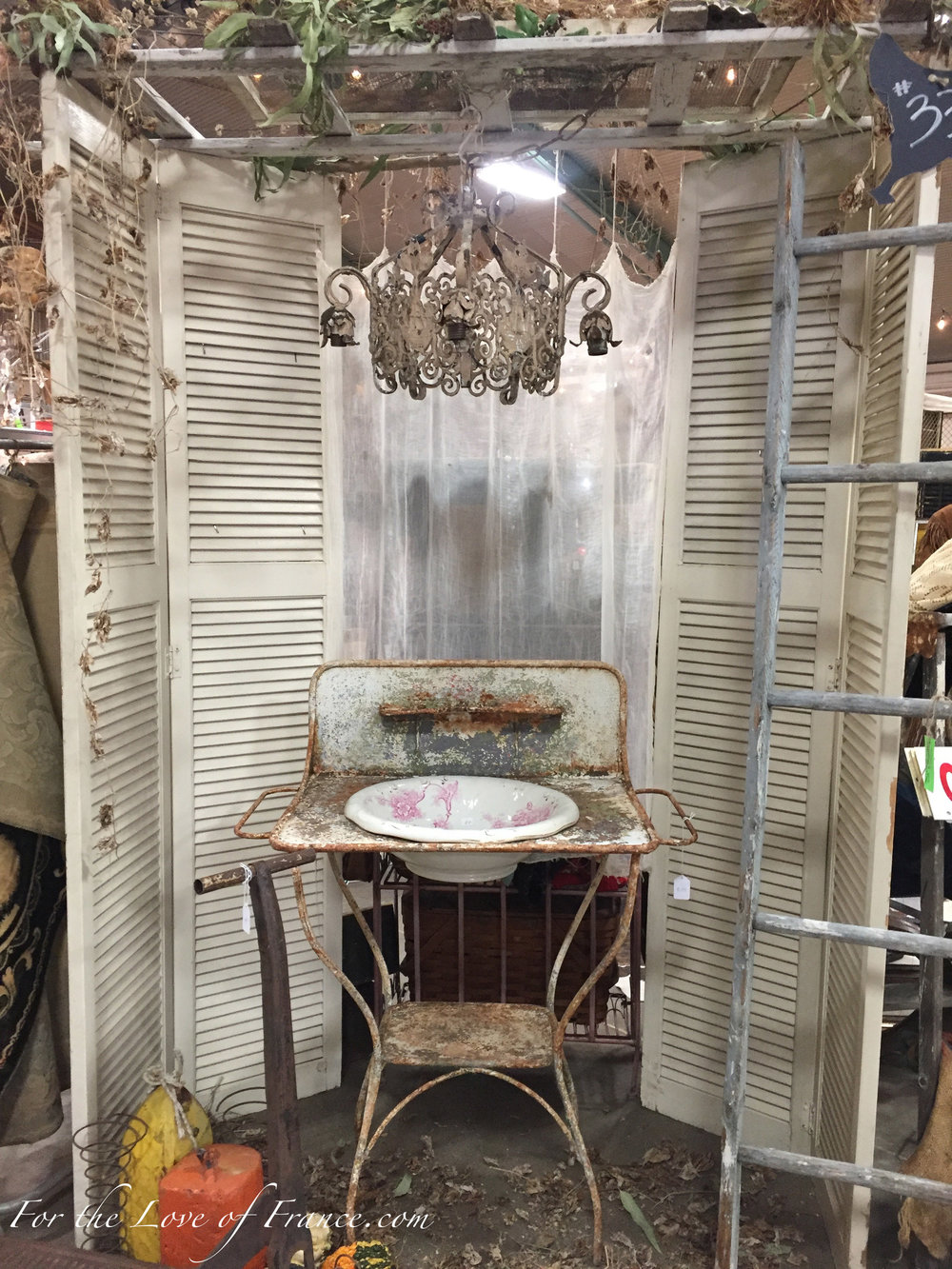 Vintage display with antique French shutters, chandelier, wash basing and stand