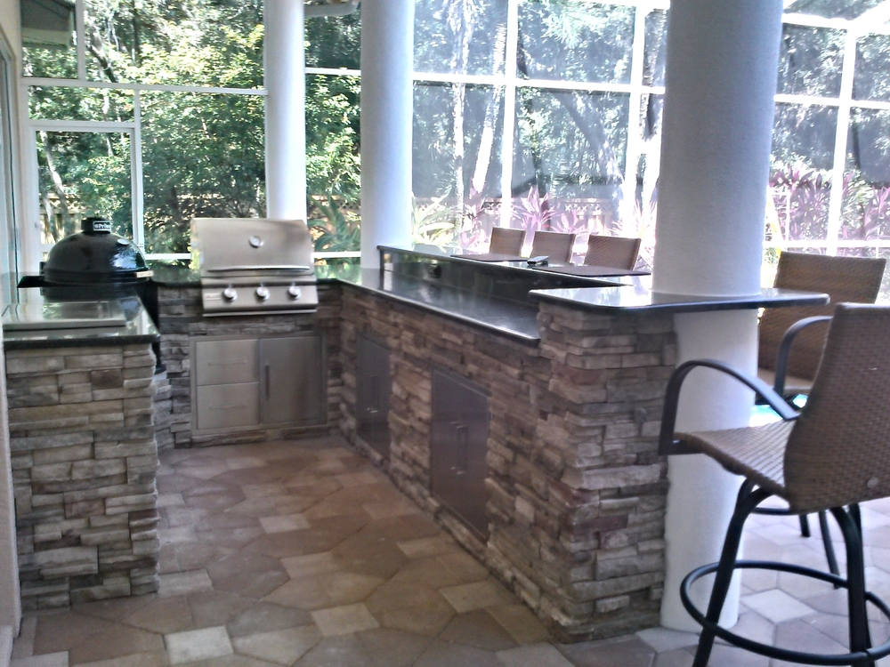 Take a look at the U-shaped outdoor kitchen. It features a raised bar with plenty of room for seating.